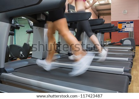 Two people running on treadmills in the gym side by side #117423487