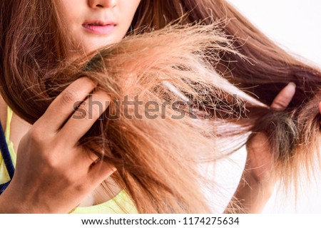 Closeup portrait of female model holding messy hair in hands, Combing with brush and pulls long hair, Daily preparation for looking nice, Long Disheveled Hair, Holding Messy Hair #1174275634