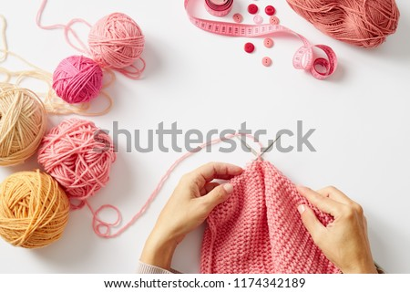 Female hands knitting with pink wool, on a white background, top view #1174342189