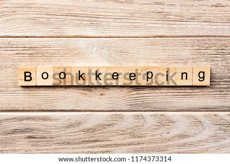 bookkeeping word written on wood block. bookkeeping text on table, concept. #1174373314