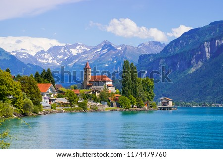 Panoramic view to the Brienz town on lake Brienz by Interlaken, Switzerland. Old fishing town with beautiful church and snow covered Alps mountains on background. Switzerland, Europe. #1174479760