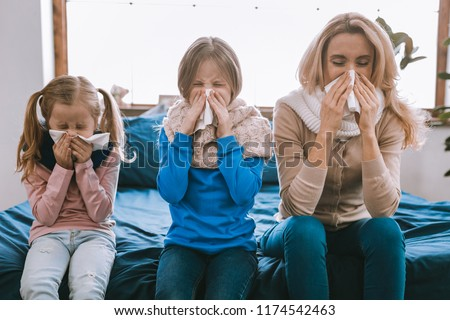 Respiratory disease. Unhappy cheerless family using paper tissues while sneezing Royalty-Free Stock Photo #1174542463