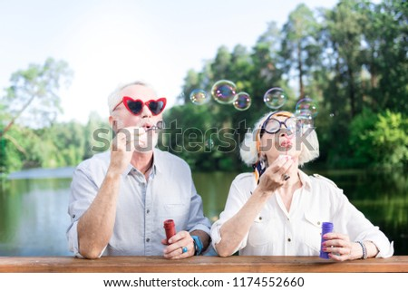 Grandfather and grandmother. Grandfather and grandmother feeling entertained while using soap bubbles of their grandchildren #1174552660