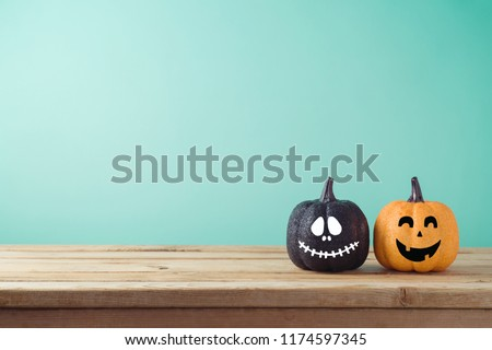 Halloween holiday concept with jack o lantern glitter pumpkin decor on wooden table #1174597345