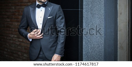 Man in custom expensive tailored tuxedo,suit posing outdoors #1174617817