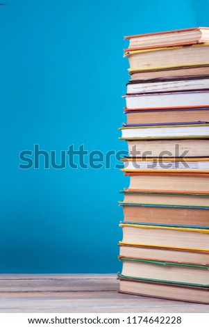 Stack of colorful real books on blue background, partial view. Back to school. Copy Space. Education background #1174642228