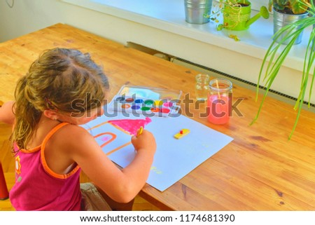 Little girl painting simple picture. Cute girl painting with watercolors. Window background. Selective focus and small DOF. #1174681390