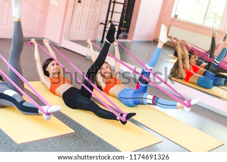 Group of young cheerful women doing exercises with fitness rubber tape #1174691326