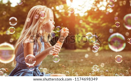 Happy little girl in autumn scenery