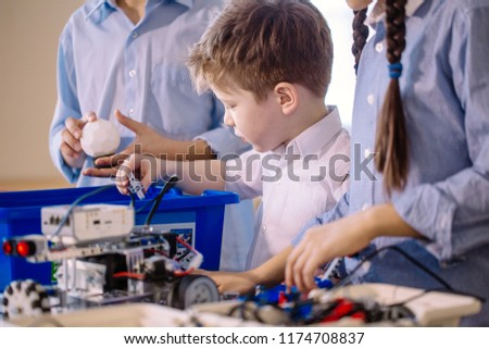 Children assambling robotic toy. Selective focus of adorable boy of 6-7 years old being busy with constructing electric robot with the help of older children. Communication and digital concept. #1174708837