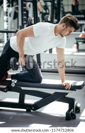 Handsome caucasian male gymnast with perfect body working out in gym doing exercises with dumbbells. #1174712806