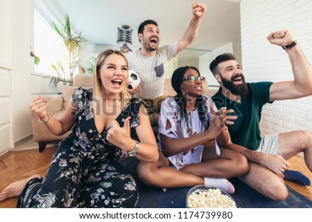 Happy friends or football fans watching soccer on tv and celebrating victory at home.Friendship, sports and entertainment concept. #1174739980