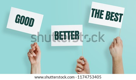 White flags with the words GOOD, BETTER, THE BEST kept in hands on a blue, pastel background. The concept of being better, developing skills, doing a better job. #1174753405