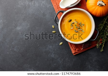 Pumpkin soup with thyme herb, cream and pumpkin seeds served in black bowl, top view #1174793686
