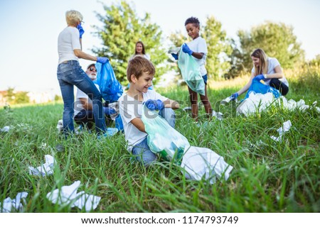 Volunteers with garbage bags cleaning up garbage outdoors - ecology concept. #1174793749