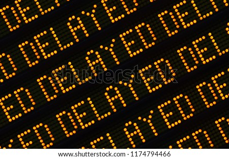 A Close Up Of The Word Delayed Repeated Multiple Times On A Sign At A Station Or Airport Or Highway Royalty-Free Stock Photo #1174794466