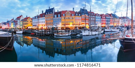 Panorama of north side of Nyhavn with colorful facades of old houses and old ships in the Old Town of Copenhagen, capital of Denmark. #1174816471