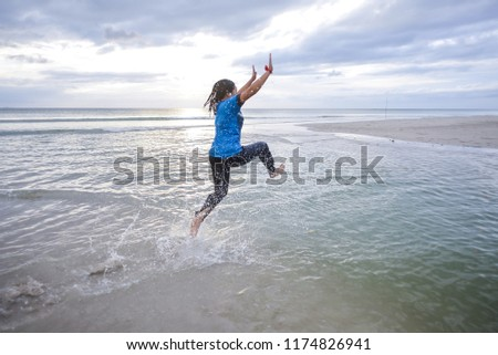 Happy girl jumping on the beach on the dawn time  #1174826941