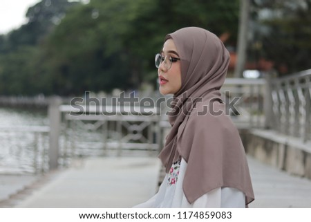 portrait of a girl wearing light chocolate color hijab in the morning at park #1174859083
