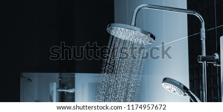 Close up of Water flowing from shower in the bathroom interior Royalty-Free Stock Photo #1174957672