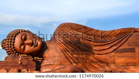 Lying Buddha statue made of teak wood with blue sky background.