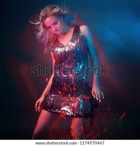Bright and stylish young woman dancing in club, color light, motion effects. Black background, long exposure #1174970467