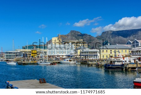 Bright color city and landscape panoramic view of the Table Mountain,Cape Town,South Africa, seen from V&A Waterfront with clock tower,boats in the sea harbor,bright sunny day,blue sky,clouds  Royalty-Free Stock Photo #1174971685