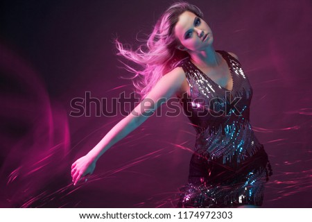 Attractive dancing blonde in the club, neon light, motion effects. Black background, long exposure #1174972303