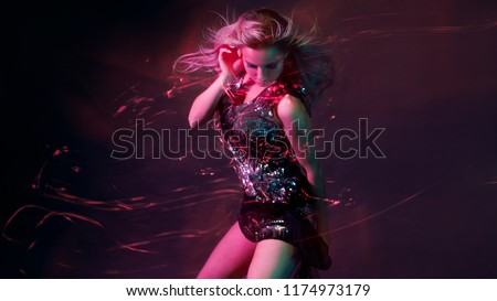 Bright and stylish young woman dancing in club, color light, motion effects. Black background, long exposure