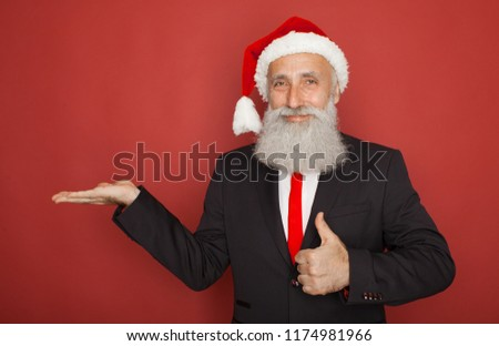Senior man in santa hat an suit presenting something on a red wall, smiling for the camera. Xmas concept. #1174981966