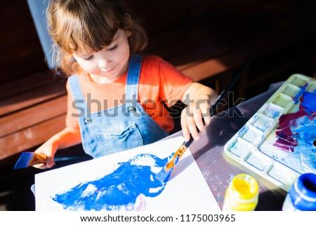 Adorable little kid girl holding paint brushes, painting picrure at the paper. Artistic preschooler, art for children