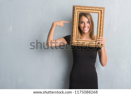 Beautiful young woman over grunge grey wall holding vintage frame very happy pointing with hand and finger