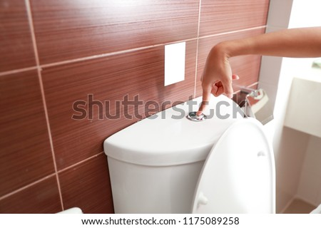 woman hand flush toilet after using #1175089258