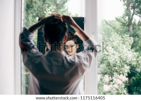 Beautiful young woman looking herself reflection in mirror checking hairstyle #1175116405