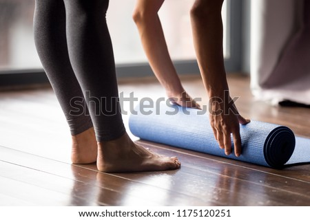 Time for meditation, fitness session, well-being concept. Girl wearing grey sporty pants rolling fitness mat before, after class in yoga studio club or at home on wooden floor. Hands and legs close up #1175120251