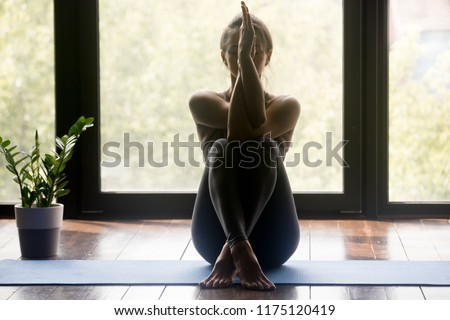 Young sporty attractive woman practicing yoga, doing Garudasana arms exercise, Eagle pose, working out, wearing sportswear, grey pants and top, indoor full length, yoga studio #1175120419