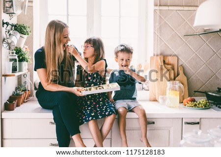 Mom with her two children sitting on the kitchen table and eating candies. Mother with daughter and toddler son having breakfast at home. Happy lifestyle family moments. #1175128183