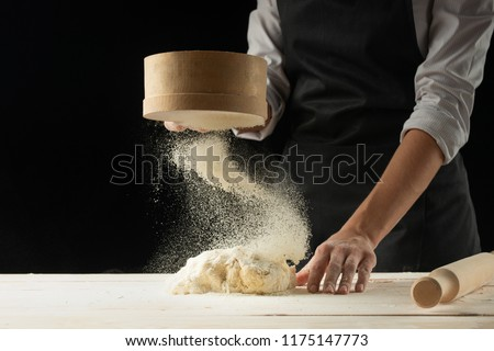 Bakery. Man preparing bread, Easter cake, Easter bread or cross-buns on wooden table in a bakery close up. Man preparing bread dough. #1175147773