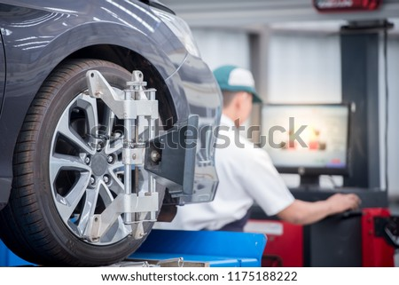 Closed up of an auto wheel : computer wheel alignment. Balancing tire wheel machine. Tyre assembling. Tyre balancing of modern car in workshop. #1175188222