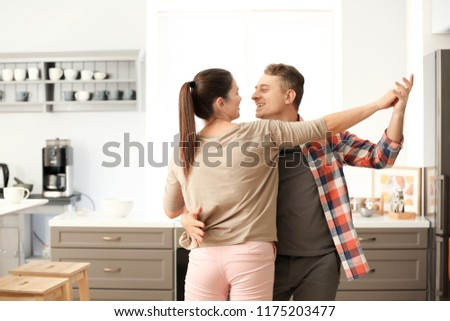 Lovely couple dancing together in kitchen #1175203477