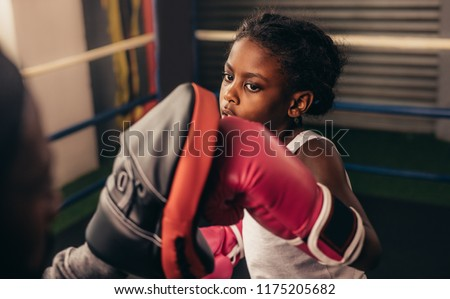 Close up of a kid training inside a boxing ring. Kid boxer wearing boxing gloves practicing punches on a punching pad. #1175205682