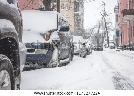 Snowstorm in the city. Froze auto cover with snow #1175279224