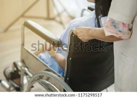 Female doctor pushing injury woman her bone crash the leg, The doctor helathcare recovery the girl sit on wheelchair #1175298517