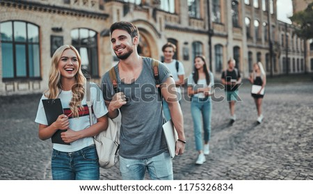 Group of young people are studying together in university. Students outdoors. Royalty-Free Stock Photo #1175326834