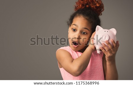 Little black girl with piggy bank, studio shot, copy space #1175368996