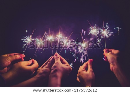 Beautiful sparklers in people hands on black background,holiday and xmas and new year concept. #1175392612