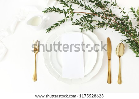 Festive wedding, birthday table setting with golden cutlery, eucalyptus parvifolia branch, porcelain plate, milk and  silk ribbon. Blank card mockup. Rustic restaurant menu concept. Flat lay, top view #1175528623