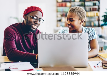 African american couple browse website on laptop computer making shopping online together at home interior, positive dark skinned hipster guy showing new app for netbook sitting at his girlfriend