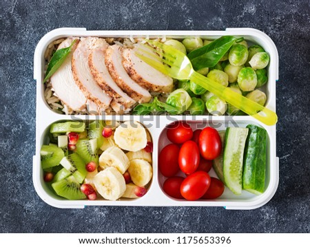 Healthy green meal prep containers with chicken fillet, rice, brussels sprouts, vegetables and fruits overhead shot with copy space. Dinner in lunch box. Top view. Flat lay #1175653396