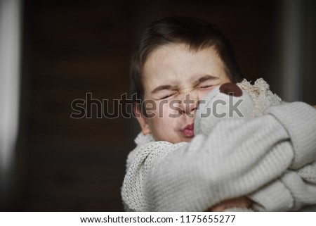 Portrait, a young boy in a white sweater hugs his favorite teddy bear toy, sincere emotions of joy, a smile of happiness on the face of the child. #1175655277
